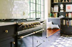 Gamma Black Lacanche in una cucina moderna con accenti di ottone, pavimento di piastrelle di cemento e metropolitana piastrelle bianche backsplash
