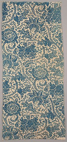 Textile, 18th century Length from a quilt, of white hand-woven cotton resist printed in blue. Design of ascending curving vine with large flower heads and branching foliage; the leaves are deeply indented, with spiny stems. Lined with bands of white dimity alternating with blue striped cotton.
