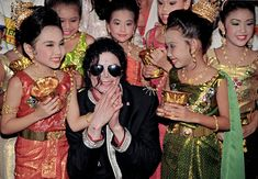Michael Jackson is greeted by children in traditional dress as he arrives ahead of his 1996 concert in Bangkok. Photo: Charles Dharapak / Associated Press