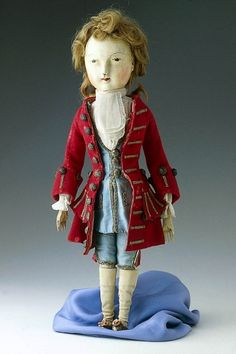 Male doll dressed in blue satin waistcoat and breeches, red wool coat, linen shirt and cravat, silk stockings, leather shoes.