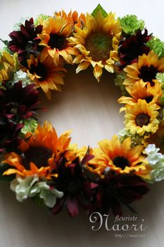 The burgundy adds a nice contrast to the yellow and orange.  This designer has created a wreath which looks so natural.....I almost believe that they grew this way :) ~Sunflower wreath  ひまわりのリース  artificial flower  20130607