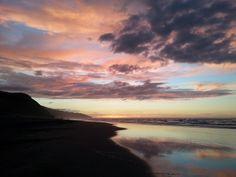New Zealand, Raglan, sunset over volcanic black sand beach
