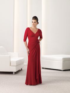 Stretch illusion mock-wrap A-line dress with three-quarter length sleeves, front and back V-necklines, ruched bodice accented with hand-crafted flower and flowing side drape. Sizes:4 – 20, 16W – 26W