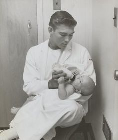 Student Nurse holding baby in his lap, 1950s?
