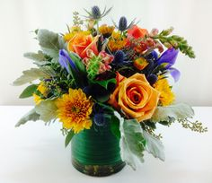 Fall is all about bold harvest colors like yellow, orange, rust, burgundy and brown.  Want to really make them pop? Add a contrasting color like deep blue or purple.  We've mixed orange roses, snapdragons, and mums with purple iris and thistle.  For greenery we've used dusty miller.  Flowers by A Floral Affair - www.afloralaffair.com. #Thanksgiving #Autumn #centerpiece