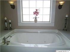 Simple travertine border adds elegance to a garden tub for Garden tub vs standard tub