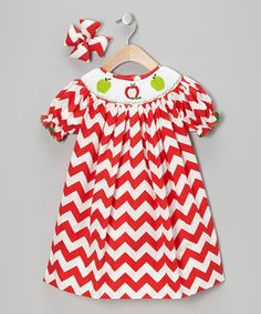 Designed with a smocked neckline and convenient back buttons, this timeless piece radiates with sweetness and goes on easy. A cushy, coordinating bow finishes the look.