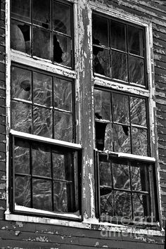 old abandon building with broken panes, the snow covered branches reflections