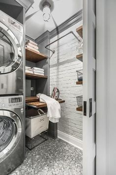 Beautifully appointed gray industrial laundry room is equipped with a stacked gray front loading washer and dryer enclosed beside floating wood and metal shelves fixed above a pull out ironing table positioned over a laundry basket placed on gray penny tiles.
