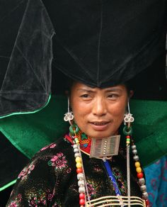 Asia | Black Yi woman with a traditional decorated hat | Yunnan, China
