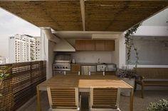 Para criar o espaço gourmet na cobertura, uma parte do terraço ganhou uma cobertura de bambu com estrutura metálica. O guarda-corpo ganhou um painel de lambris de madeira e o piso foi revestido por placas cimentícias com fulget, da Pietra. Na cozinha, executada por José Pillon, os equipamentos da Viking ficam embutido. Os móveis de madeira são da Saccaro. Repare à direita o janelão envidraçado, idealizado para iluminar o vão da escada