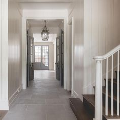 Beautiful home features white shiplap walls accented with gray double doors as well as light gray staggered tiled floors illuminated by iron and glass lanterns.