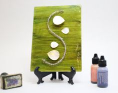 """This piece of art features a """"S"""" shape stream of glass beads. Four petrified wood beads add even more bling. The inked background is of various shades of green. Pretty."""