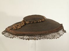 1750-1760, hat made from split straw plait in a chequered pattern of black and natural straw, trimmed with a fancy plait just inside the brim, and there is a garland of split straw cord and tassles around the crown. There is a band of macrame straw braid (possibly Swiss) with split straw decorations around the brim edge. The black elasticated tape is a later addition. Date uncertain. Could be Swiss.  Snowshill Manor © National Trust / Richard Blakey