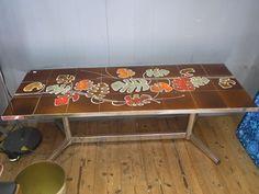 Retro tegel salontafel met blad met bruine achtergrond en gekleurde bladermotief. Onderstel van zilver metaal. Vraagprijs € 125.00.