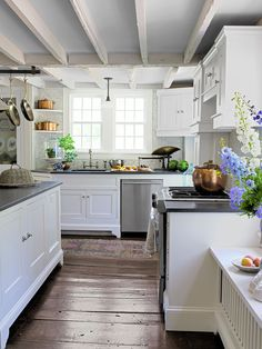Although she's inspired by things that are old, Ellen's style is anything but stale. With cheerful pops of color and pattern-on-pattern layering, her home exudes a youthful energy while retaining elements of its historic charm. In this photo: The kitchen features exposed joists and uneven, wide-plank floors. Related: The Ultimate Guide to Kitchen Design   - CountryLiving.com
