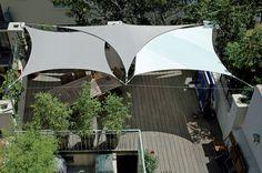 Panaché de voiles d'ombrage Sunbrella® et teintes neutres, protégeant la terrasse de part et d'autres. Réalisation Exonido (Charbonnières)