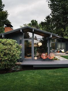 Exterior elevation of Portland midcentury renovated house with outdoor wall sconces and chairs on patio