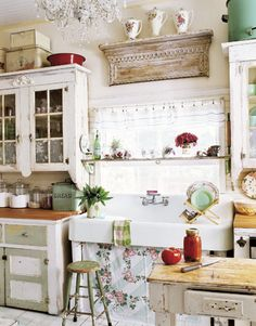 This New Jersey homeowner upped the charm quotient of her glass-front cabinets by tacking lacy organza napkins inside the bottom panes. An old porcelain sink rests atop porch posts framing a vintage-tablecloth skirt. Mismatched lower cabinets are topped with new butcher-block countertops; one was retrofitted to house the dishwasher.