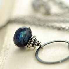This blue labradorite gemstone necklace features a lovely plump spectrolite briolette dangling from an artisan crafted sterling silver ring and shimmering gray labradorite rondelle, all hanging from delicate sterling silver chain.  Spectrolite is a gorgeous and intriguing gem with a beautiful deep midnight navy color and subtle shimmer.Necklace measures 16 inches (40.6 cm) around plus an additional 3 inch (7 cm) extender.  The briolette is about 9 mm x 9 mm, and the circle is 5/8 inch (1.6…