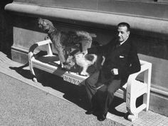 President of Uruguay, Alfredo Baldomir, sitting on a bench at his Presidential residence with his dogs. c. 1941