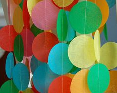 """Garland is made with an 11 color mix of bright rainbow colors  <><><><><>  These festive tissue garlands will add a whimsical and bright touch to any celebration. The 12 foot strand can be cut and used a variety of ways:  *hang short strands from balloons* *use as a backdrop to a treat table or a photo shoot* *dress up a plain table* *swoop them across the room for an airy effect*  Listing is for one 12 foot garland of fifty-five 2 ½ """" tissue paper dots that have..."""