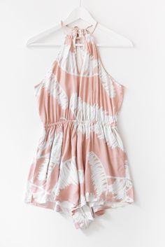 Blush pink botanical print romper with a halter neckline and tie back…