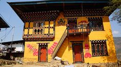 Huis in Bhutan, met fallussen ter bescherming tegen de boze geesten. Kijk voor meer reisinspiratie op www.nativetravel.nl