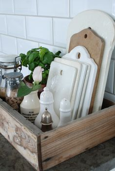 Keep kitchen clutter at bay by corralling frequently used items in a tray or beautiful vintage box like this one. Include a few beauty pieces, like these vintage cutting boards to make it pretty.