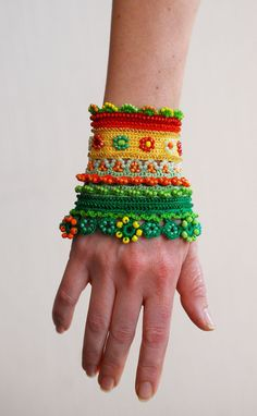 Handmade crochet cuff in red, orange, yellow and green colors. It is decorated with lots of glass beads. This cuff is made of high quality