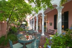 """Meeting Street Inn ~ Charleston. In the style of the Charleston single house, the luxury inn's fifty six guest rooms open to sunny piazzas overlooking a garden courtyard. Each room features antique reproduction furnishings and four poster """"rice"""" beds."""