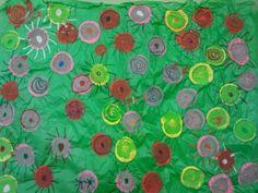 Paper de seda, a damunt pintam cercles amb tempera i quan esta eixut i feim els petals amb ceres