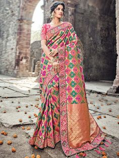 Fascinating golden, pink, green banarasi silk saree with work patch border and tussles will give yourself charming look. Eye-catching outfit will add a regal touch to your personality.