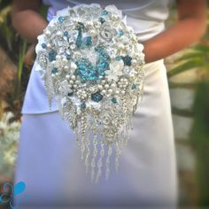 THIS IS THE BOUQUET BUT MADE BY ME DARK BLUE INSTEAD OF WHITE, IVORY INSTEAD OF TURQUOISE, SILVER BROOCHES