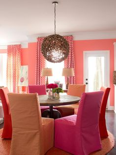 To give this open space between the living room and eat-in kitchen practical use, it was designed as a casual, colorful breakfast nook. A round table and round rug keep traffic flowing easily between the two main spaces. Anytime you're working with a boxy space, consider adding rounded pieces to soften the hard lines.