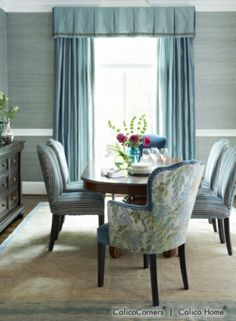 A bit too formal at the window...but like the playfulness of three different fabrics on upholstered dining room chairs.