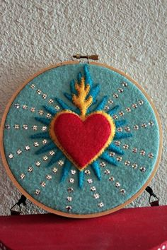 Here's my finished felt sacred heart. Sewing the sequins on wasn't half as tedious as I thought it would be!krakatoakatie: Here's my finished felt sacred heart. Sewing the sequins on wasn't half as tedious as I thought it would be! Felt Embroidery, Cross Stitch Embroidery, Embroidery Patterns, Felt Applique, Mexican Crafts, Mexican Folk Art, Catholic Crafts, Kids Crafts, Arts And Crafts