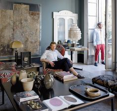The designers Britt Moran (seated) and Emiliano Salci in one of their apartment's two sitting rooms. A 1960s Verner Panton pendant, luxuriou...