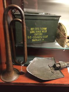 The bugle is from just after World War II, the field shovel is battle used in World War II and the ammo box is reconditioned from the first Gulf War. Shovel, World War Ii, Battle, Box, World War Two, Dustpan, Snare Drum, Wwii