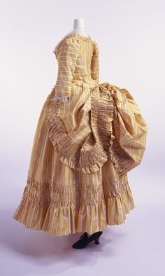 "Robe à la polonaise with Matching Petticoat: ca. 1780, French, striped silk taffeta. ""The robe à la polonaise came to popularity in the 1770s. The skirt was held up by cords and divided into three panels of full drapes over the underskirt. In the late 18th century, following the trend toward simple clothing except for court dress, women's costumes also became more casual."""