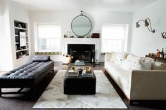 Beautiful living room features a cream sofa with high-back adorned with John Robshaw Sheesha Pillows facing a black leather tufted bench across from a black industrial coffee table atop Restoration Hardware Diamond Cowhide Rug. A hoop mirror leans against a fireplace mantle flanked by built-in window seats topped with yellow and gray cushions in Kelly Wearstler Bengal Bazaar Bronze fabric under windows dressed in white roller shades.