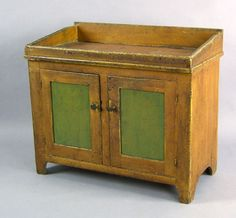 """Pennsylvania painted drysink, mid 19th c., with 2 recessed panel doors and cutout feet, retaining an old ochre surface with green panels, 33 1/2"""" h., 38"""" w."""