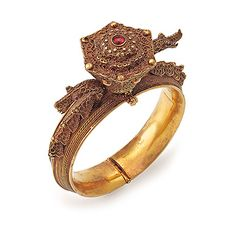 AN IMPRESSIVE GOLD BANGLE          Designed as a hinged engraved bangle, centering on a stylized hexagonal crown, set with a single ruby cabochon, and accented with designs in gold filigree and wire-work, flanked by two similarly accented stylized dragons, with cabochon gemstone eyes, mounted in gold, c. 1930s #Vintagejewellery #AngadiSilks #AngadiSilksBangalore angadisilks.com #Angadi Silks Traditional Indian Jewellery, South Indian Jewellery, Ethnic Jewelry, Indian Jewelry, Vintage Jewellery, Antique Jewelry, Gold C, Pakistani Jewelry, Gold Bangles Design