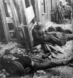 Soviet soldiers resting among the dead during a lull in the Battle of Berlin, 1945