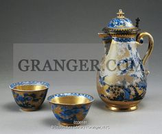 This is a Granger licensable image titled 'DECORATIVE ARTS.  Little cups and coffee pot with blue blossoming branches and birds on a gold background, porcelain, Meissen manufacture, Saxony. Germany, 18th century. Full credit: De Agostini / L. Pedicini / Granger, NYC -- All rights r' by Granger, NYC All rights reserved. You may not copy, publish, or use this image except for sample layout ('comp') use only. You must purchase the image from Granger in order to use it ...