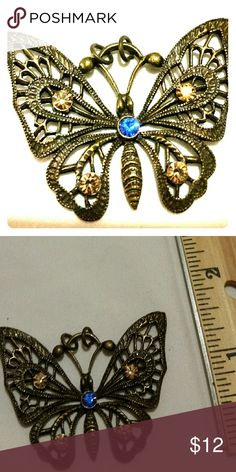 Butterfly Pendant Lovely as can be and ready to adorn your neck, this elegant butterfly pendant is of antiqued gold tone metal with topaz and blue rhinestones. Jewelry Necklaces