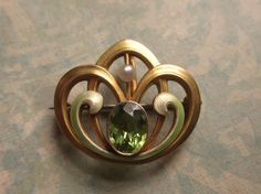 Brooch | Bippart Griscom and Osborn.  14kt gold, peridot, seed pearl and enamel.  ca. 1900.