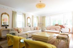 This pastel living room by Sasha Bikoff takes on a softer color palette with shades of pastel pink, yellow and nude decor.