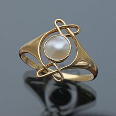 ARCHIBALD KNOX 1864-1933 Attrib. Murrle Bennett & Co Ring  Gold Pearl H: 1.5 cm (0.59 in)  Ring Size:  |UK:Q½|  |US:8.5|  |EU:58.3|  |Asia:17.5| Marks: M.B.C. & 18ct British, c.1900 Ring Case Literature: cf. Jewelry & Metalwork in the Arts & Crafts Tradition, Elyse Zorn Karlin, 1993, page 112 Theodor Fahrner Schmuck, Pforzheim, 1990 Documentation by Ulrike von Hase, pages 272-73  Ref: 7704