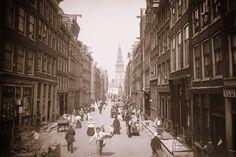 Jodenbreestraat gezien naar de Zwanenburgwal met het hoekhuis Sint Antoniesbreestraat 102 en daarachter de toren van de Zuiderkerk (ca. 1880).